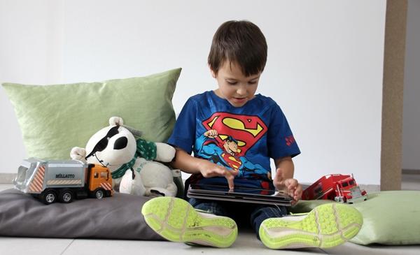 Ein Junge sitzt mit einem Tablet auf dem Boden und nutzt darauf den Möbelplaner der Schreinerei Fiegenbaum. Neben ihm liegen verschiedene Spielsachen.