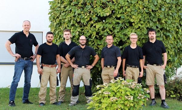 Das Team der Schreinerei Fiegenbaum im Garten der Schreinerei stehend. Von links nach rechts sind Friedrich Fiegenbaum, Mersudin Hamidovic, Michael Sailer, Tobias Dernek, Markus Belz, Michel Bauer und Johannes Braun zu sehen.