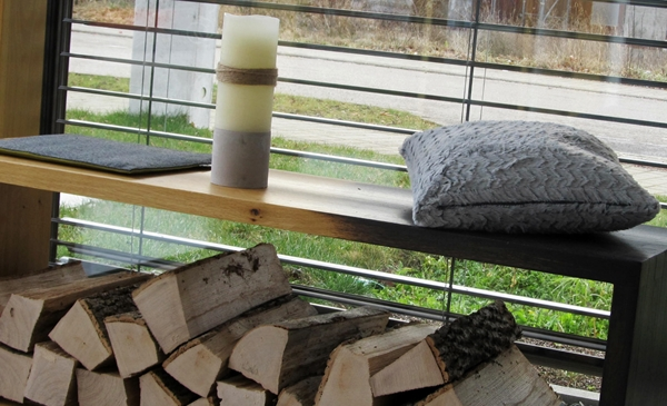 Eine Sitzbank mit Brennholz auf der ein Sitzkissen liegt