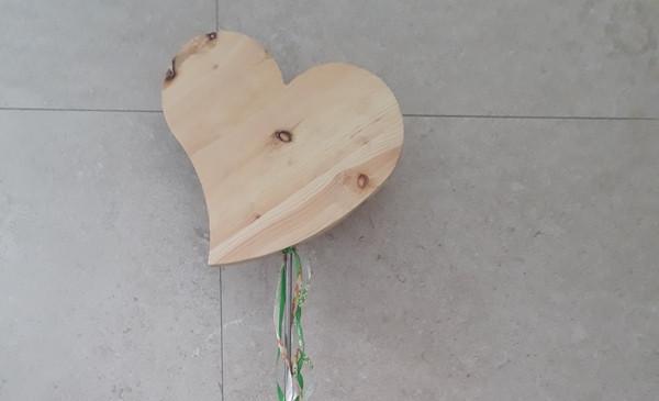 Ein Herz aus Holz vor einer Steinwand