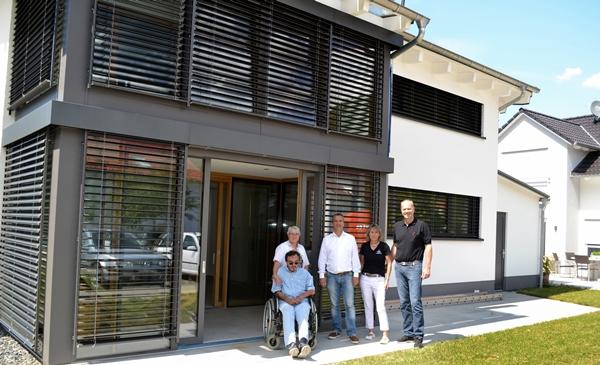 Blick auf das Biosolarhaus vor dem Michael Hennrich MdB, Mitarbeitende von ihm sowie Birgit und Friedrich Fiegenbaum stehen.