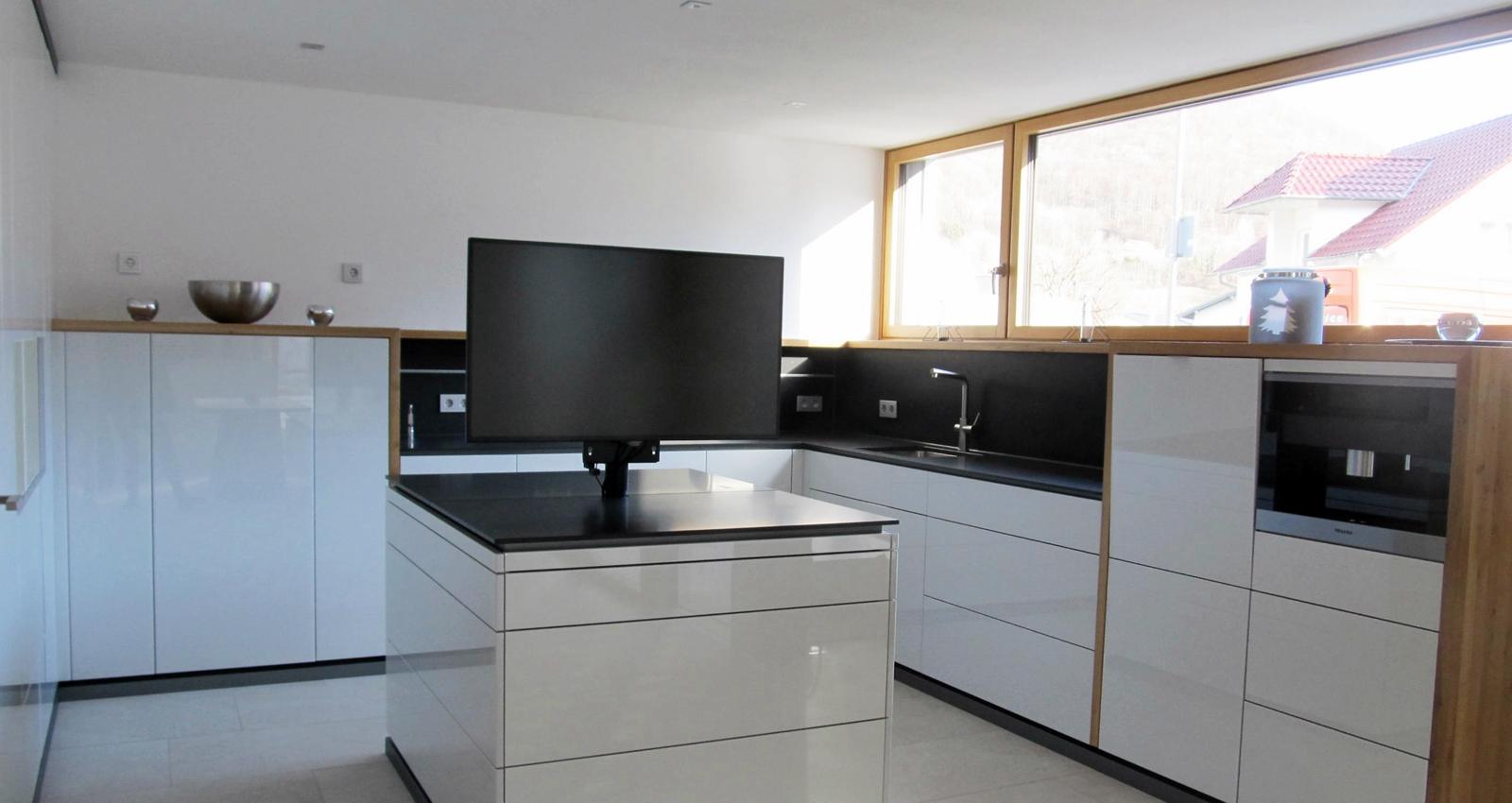 Es ist die Einbauküche im Bio-Solar-Haus der Schreinerei Fiegenbaum mit Bildschirm zu sehen