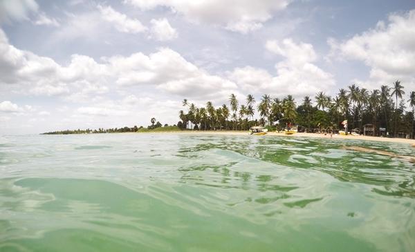 Blick vom Meer in Richtung Strand mit Palmen bei blauem Himmel