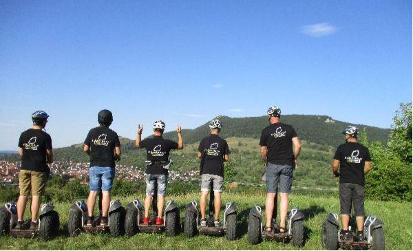 Das Team der Schreinerei Fiegenbaum steht auf Segways. Im Hintergrund ist die Teck und blauer Himmel zu sehen.